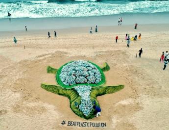 Una gigantesca tartaruga costruita sulla spiaggia con migliaia di bottiglie di plastica